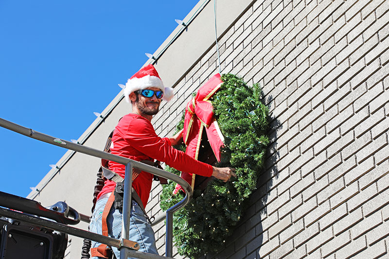 man in a Santa hat hanging a large wreath from a tree bucket